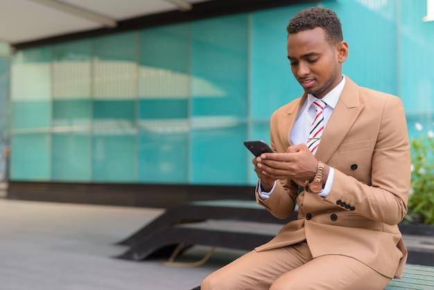 Bel giovane uomo d'affari africano utilizzando il telefono seduto fuori dall'edificio