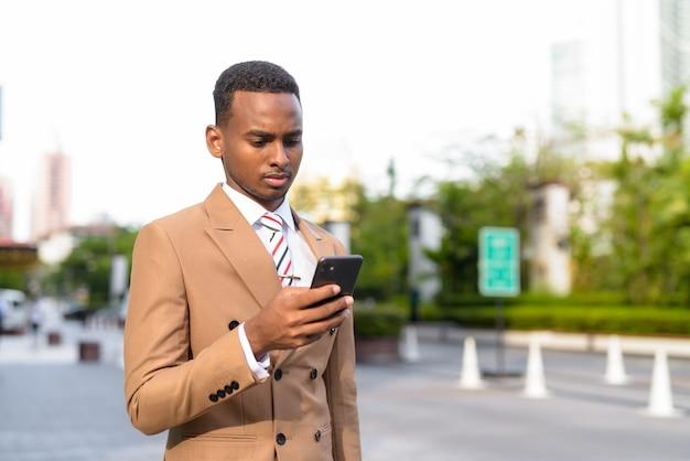 Bel giovane uomo d'affari africano utilizzando il telefono nelle strade all'aperto