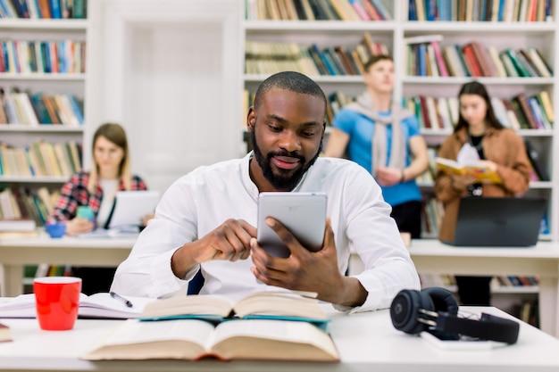 Giovane uomo felice africano bello, studente, con la barba e in camicia bianca, seduto al tavolo con i libri nella sala di lettura delle biblioteche
