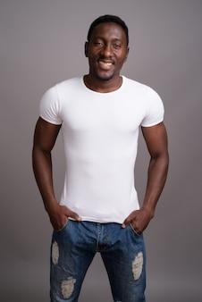 Bel giovane uomo africano su sfondo grigio