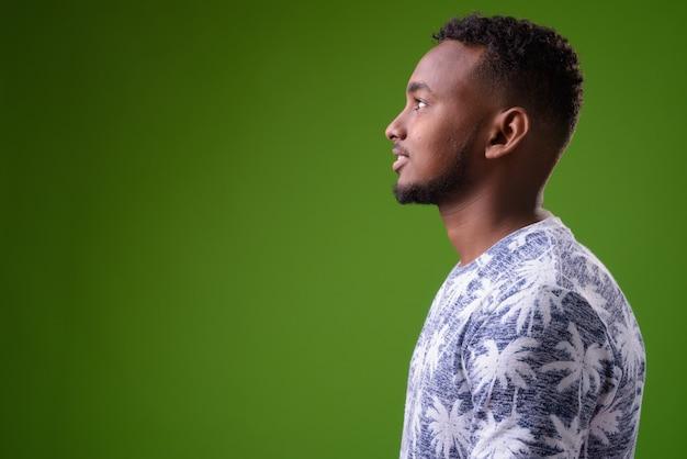 Bel giovane uomo africano contro la parete verde