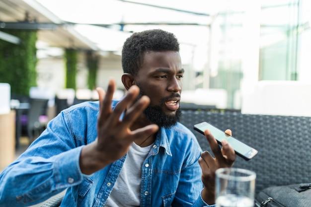 Telefono di conversazione arrabbiato del giovane uomo africano bello sull'altoparlante nella caffetteria
