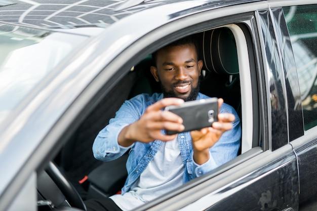 Il giovane uomo africano bello prende la foto sul telefono mentre guida la sua automobile