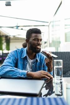 Il giovane uomo africano bello parla al telefono sull'altoparlante nella caffetteria
