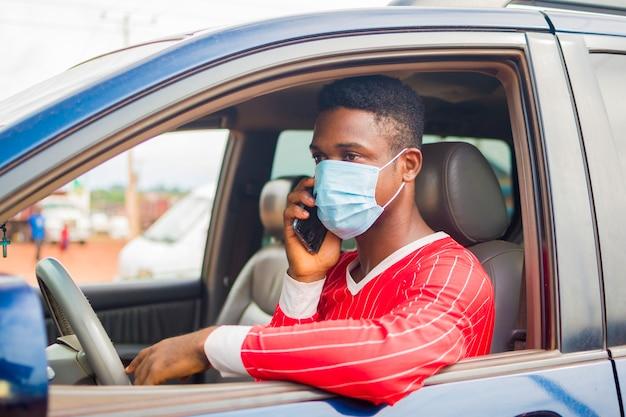 Il giovane tassista africano bello che indossa la maschera per il viso previene, previene, si impedisce lo scoppio nella società e chiama con il suo telefono cellulare