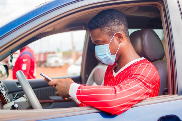 Il giovane tassista africano bello che indossa la maschera facciale che previene, previene, si impedisce lo scoppio nella società e gestisce il suo telefono cellulare