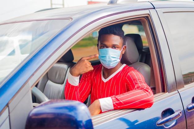 Il giovane tassista africano bello che indossa la maschera facciale che previene, previene, si è impedito lo scoppio nella società