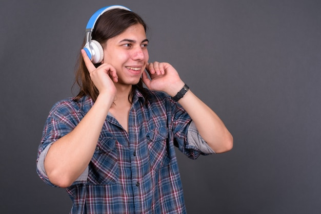Giovane uomo bello hipster androgino con i capelli lunghi contro il muro grigio