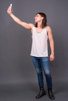 Giovane uomo androgino bello con i capelli lunghi contro il muro grigio
