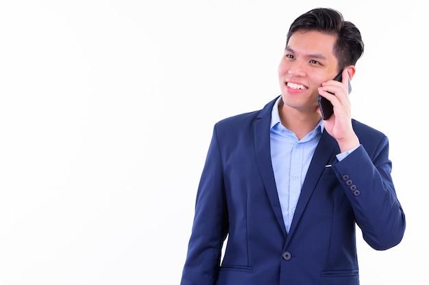 Vestito da portare giovane uomo d'affari asiatico bello isolato contro il muro bianco