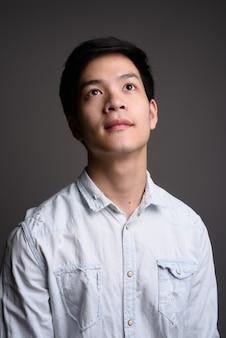 Giovane uomo d'affari asiatico bello che indossa camicia bianca su grigio
