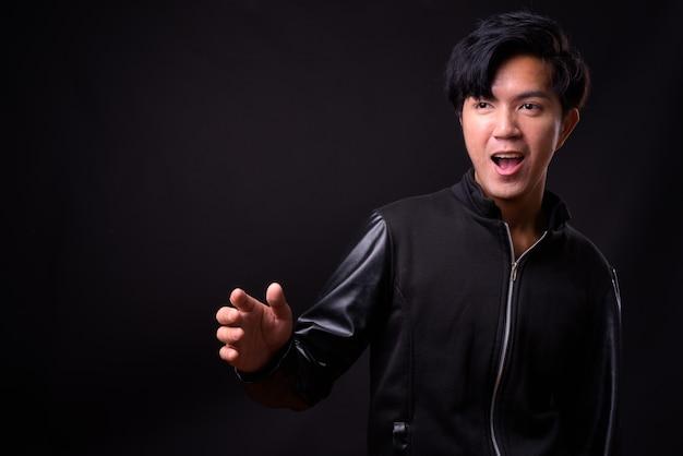 Giovane uomo asiatico bello sul nero