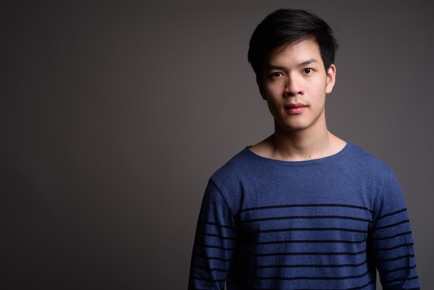 Bel giovane uomo asiatico su grigio