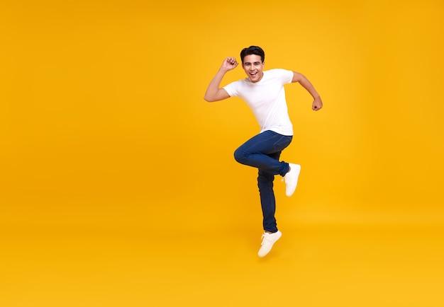 Giovane uomo asiatico bello che sorride e che salta mentre celebra il successo isolato sul giallo.