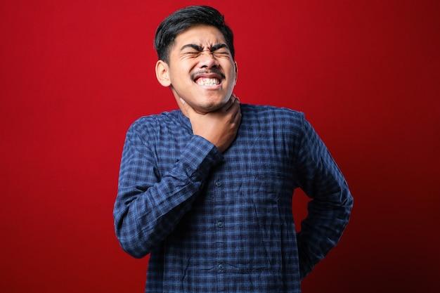 Giovane uomo asiatico bello che indossa una camicia casual su sfondo rosso isolato che grida e soffoca perché strangola dolorosamente. problema di salute. asfissia e concetto di suicidio.