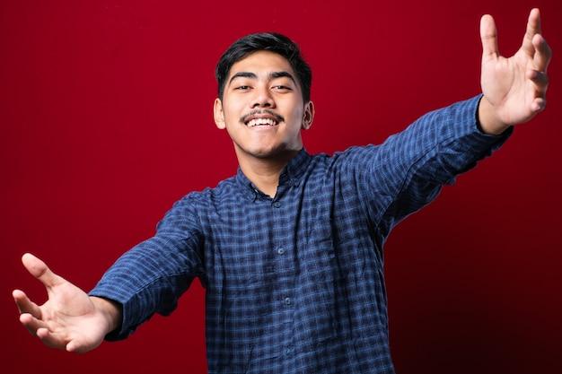 Giovane uomo asiatico bello che indossa una camicia casual guardando la telecamera sorridendo a braccia aperte per l'abbraccio. espressione allegra che abbraccia la felicità su sfondo rosso
