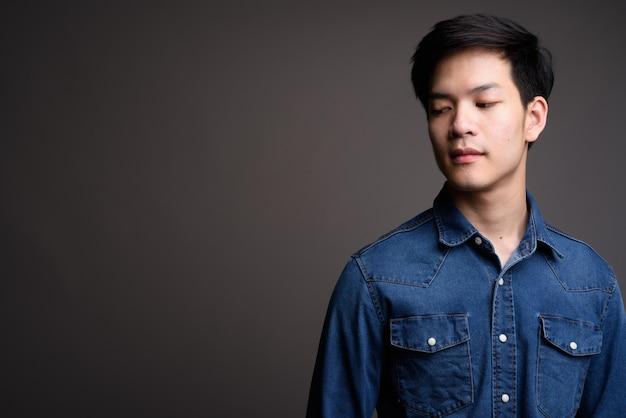 Giovane uomo asiatico bello che indossa la camicia di jeans su grigio
