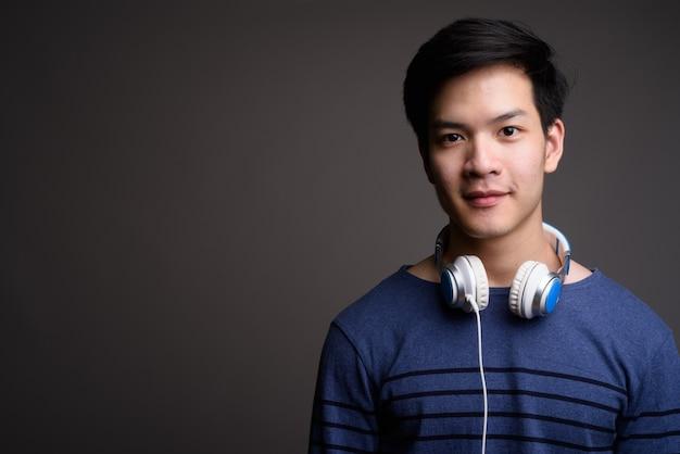 Giovane uomo asiatico bello che indossa le cuffie su grigio