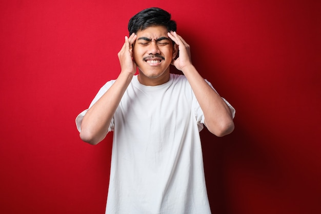 Giovane uomo asiatico bello che indossa una maglietta bianca in piedi su uno sfondo rosso isolato con la mano sulla testa per il dolore alla testa a causa dello stress. soffrendo di emicrania.
