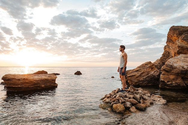 Giovane atleta bello in piedi sulla spiaggia rocciosa in riva al mare