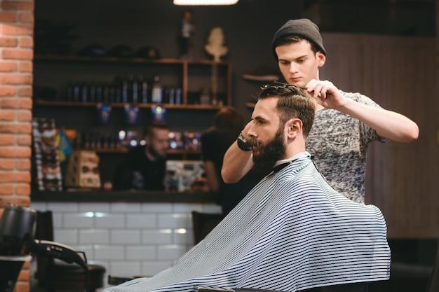 Giovane barbiere bello che fa taglio di capelli di uomo barbuto attraente nel negozio di barbiere