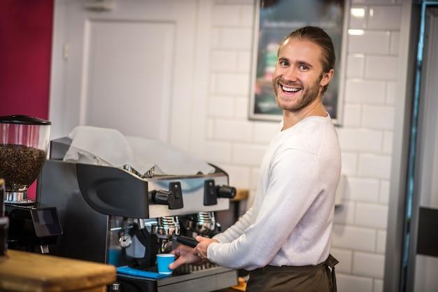 Giovane barista bello che prepara caffè