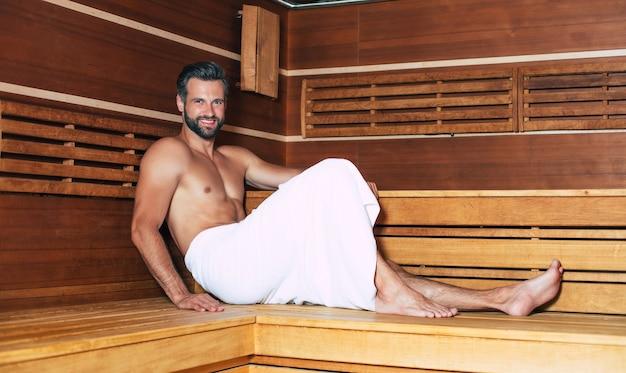 Giovane uomo bello con la barba nel telo da bagno è rilassante nella sauna calda durante le vacanze