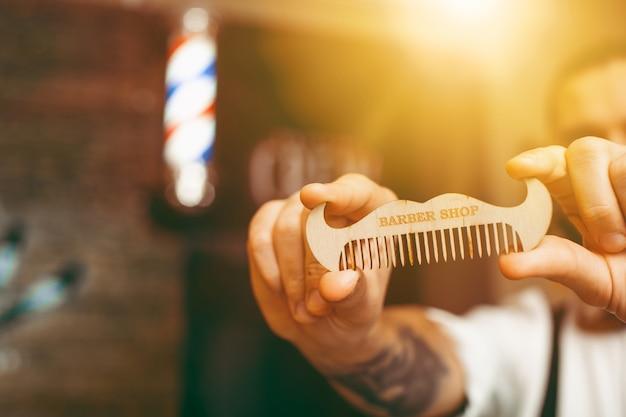 Giovane bel barbiere con un pettine a forma di baffi in mano