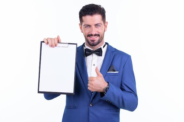 Giovane uomo d'affari barbuto bello che indossa tuta isolata contro il muro bianco