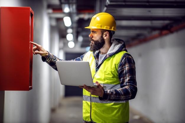 Giovane elettricista barbuto bello in piedi nella costruzione nel processo di ricostruzione con il computer portatile in mano e controllando la scatola di distribuzione.