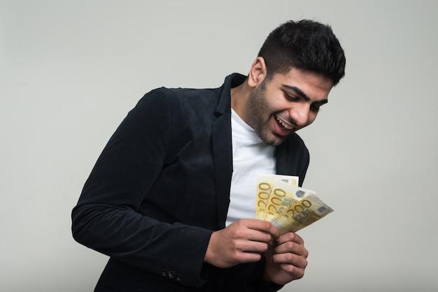 Giovane uomo d'affari indiano barbuto bello contro il muro bianco