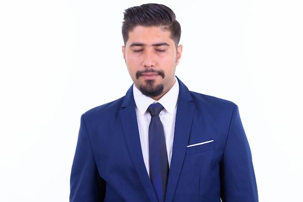 Giovane uomo d'affari iraniano barbuto bello in vestito isolato su bianco