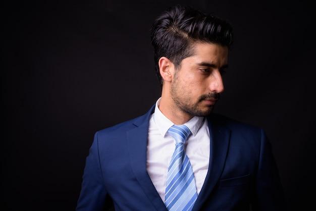 Giovane uomo d'affari persiano barbuto bello sul nero