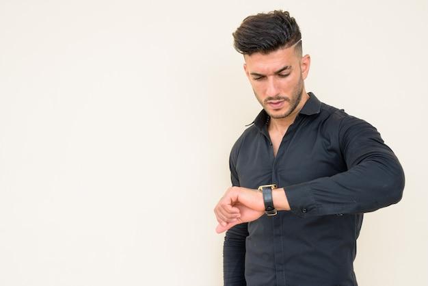 Giovane uomo d'affari persiano barbuto bello che controlla il tempo