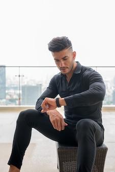 Giovane uomo d'affari persiano barbuto bello seduto e controllando il tempo in città