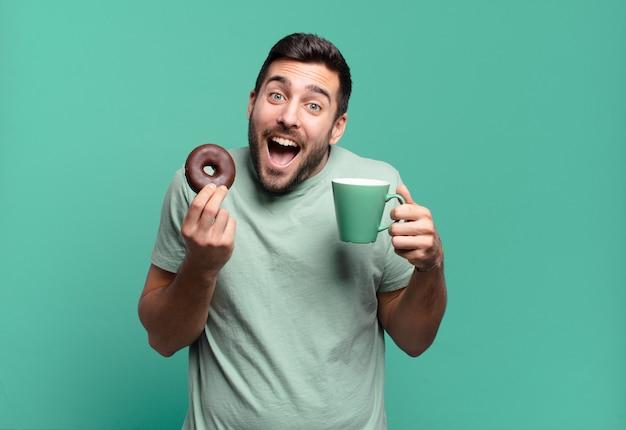 Giovane uomo biondo bello con una ciambella al cioccolato e una tazza di caffè. concetto di colazione