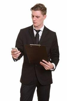 Giovane uomo d'affari biondo bello in vestito che tiene appunti e utilizzando il telefono