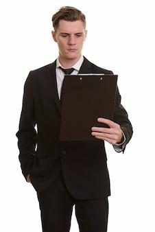Giovane uomo d'affari biondo bello in vestito che tiene appunti