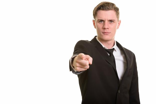 Giovane uomo d'affari biondo bello in vestito che indica alla macchina fotografica