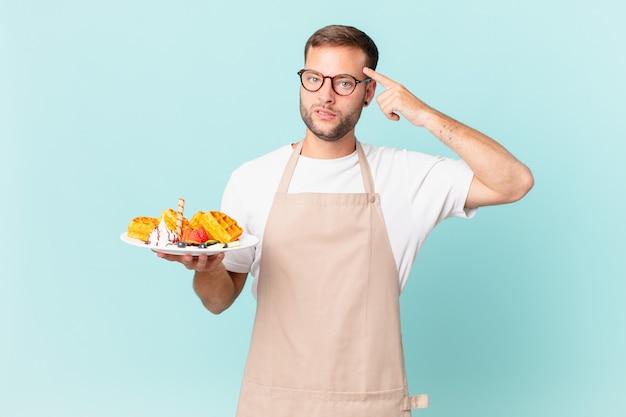 Giovane bell'uomo biondo che si sente confuso e perplesso, mostrando che sei pazzo. cucinare il concetto di waffle