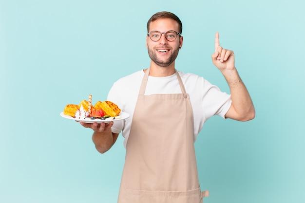 Giovane bell'uomo biondo che si sente un genio felice ed eccitato dopo aver realizzato un'idea. cucinare il concetto di waffle