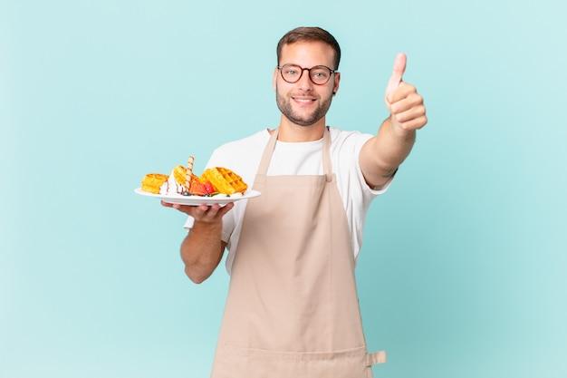 Giovane uomo biondo bello sentirsi orgoglioso, sorridendo positivamente con i pollici in su. cucinare il concetto di waffle