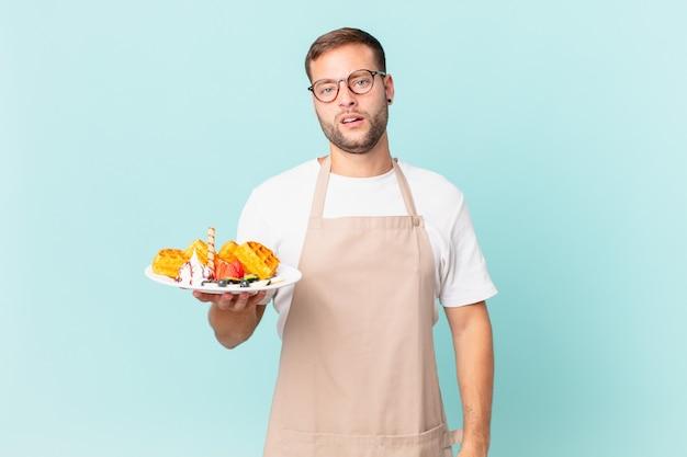 Giovane uomo biondo bello sentirsi perplesso e confuso. cucinare il concetto di waffle