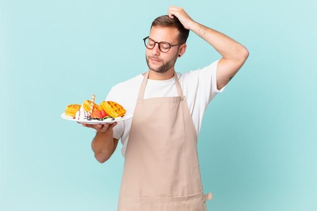 Giovane uomo biondo bello sentirsi perplesso e confuso, grattandosi la testa. cucinare il concetto di waffle