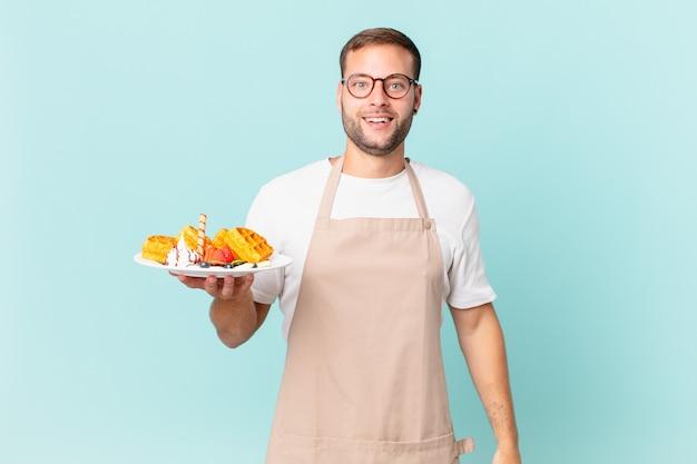 Giovane uomo biondo bello che sembra felice e piacevolmente sorpreso. cucinare il concetto di waffle