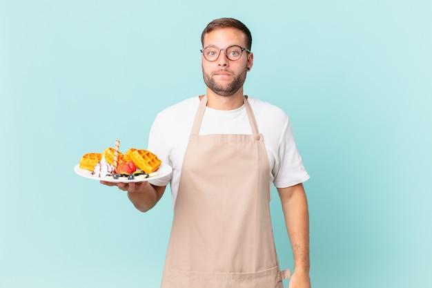 Giovane uomo biondo bello che sembra perplesso e confuso. cucinare il concetto di waffle