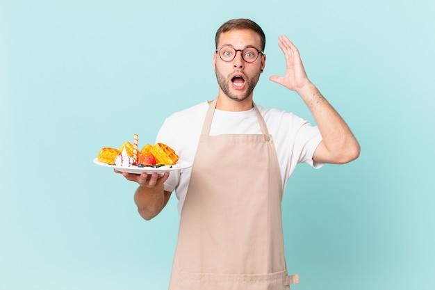 Giovane uomo biondo bello che grida con le mani in aria. cucinare il concetto di waffle