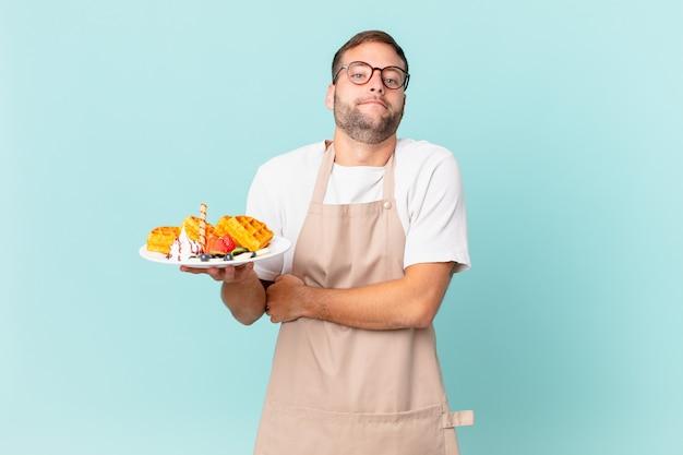 Giovane uomo biondo bello che scrolla le spalle, sentendosi confuso e incerto. cucinare il concetto di waffle