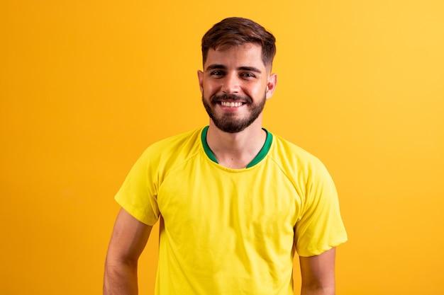Giovane bel ragazzo vestito per il gioco del brasile. uomo vestito per la coppa del mondo