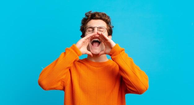 Giovane bel ragazzo che si sente felice, eccitato e positivo, dando un grande grido con le mani vicino alla bocca, chiamando